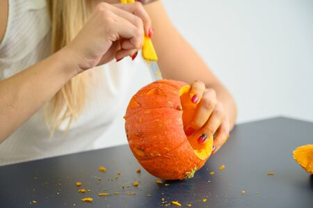 A woman cuts out a face with a stationery knife on a pumpkin for Halloween lamps on a black table. Close-up of female hands making jack-o-lantern on the eve of all saints. Front view