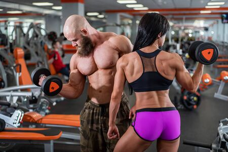Powerful, muscular, strong, man and woman, pick up the dumbbell with your hands. Nice bicep. They look in different directions. Sports hall