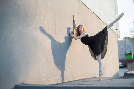 Ballerina in tutu posing standing near the wall. Beautiful young woman in black dress and pointe dancing outside. Gorgeous ballerina performing a dance outdoors Banco de Imagens