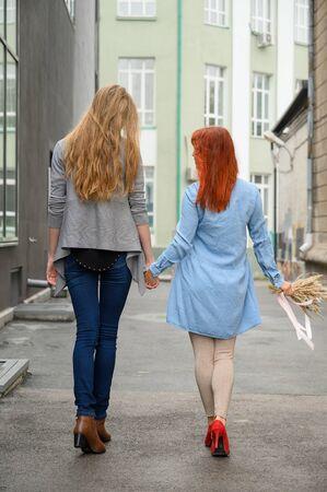 Relaciones del mismo sexo. Feliz pareja caminando por la calle cogidos de la mano. Las espaldas de dos hermosas mujeres en una cita con un ramo de flores secas. LGBT.