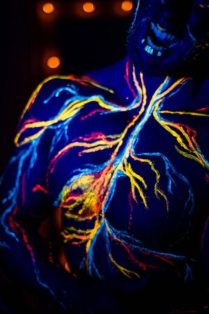 UV patterns body art of the circulatory system on a mans body. On the torso of a muscular athlete, veins and arteries are drawn with fluorescent dyes. Bodybuilder standing by the mirror with lamps.