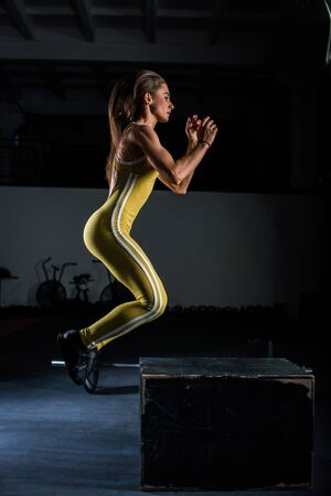 A young European girl in a yellow jumpsuit performs jumps on a wooden box in a dark gym for crossfit Stock Photo