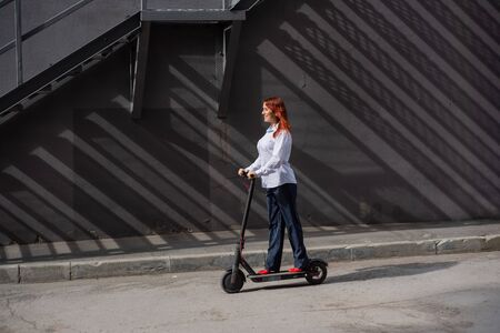 A red-haired girl in a white shirt drives an electric scooter along the wall. A business woman in a trouser suit and red high heels rides around the city in a modern car. Business woman on a scooter.