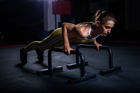 Young athletic girl in yellow tight sports uniform doing horizontal push-ups with bars in gym
