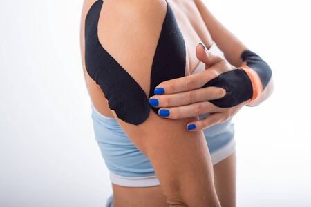 Female shoulder with kineziotape on a white background. Alternative medicine for sports injuries of joints and ligaments. Young sportswoman with medical record on a sore shoulder and wrist.