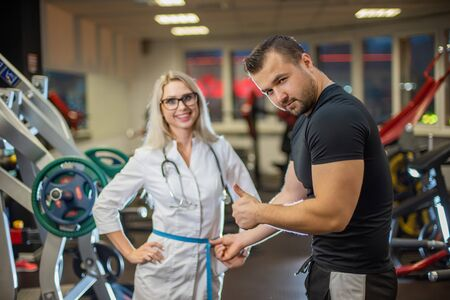 The athlete in the gym measures with a centimeter tape the waist volume of a beautiful female doctor in medical uniform. The gym coach approves the slender figure of a beautiful physiotherapist woman.