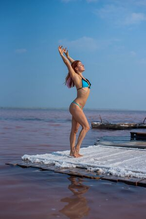 A beautiful woman in a seductive blue bikini stands on a wooden raft covered in salt. The salt lake is pink. Deposit and extraction of edible salt. Nature miracle..