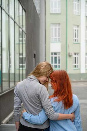 Same-sex relationships. A happy lesbian couple walked along the street and gently hug each other around the waist. The backs of two beautiful women on a date with a bouquet of dried flowers. LGBT. Stock Photo