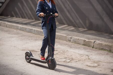 A red-haired girl in a jacket and trousers drives an electric scooter along the wall. A business woman in a pantsuit and red high heels rides around the city in a modern car. Office worker. Dress code