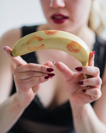 European girl holding a fresh banana with red lipstick traces. The concept of oral sex