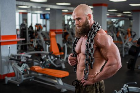 A bald, bearded bodybuilder with large relief muscles holds a heavy thick chain in his hands. Bright gym. Фото со стока