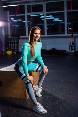 A beautiful woman in a dark room sits on a cube. The coach is resting after a productive roundabout. Female athlete in sportswear in the gym. Фото со стока