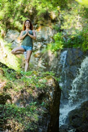 Red-haired woman in shorts doing yoga at the waterfall. A girl stands in a pose of a tree in the forest