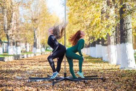 Two beautiful gymnasts do pair tricks on a portable platform in a beautiful autumn park. Two friends in the same body dance on a portable pole stage against the backdrop of autumn leaf fall. Pole dance