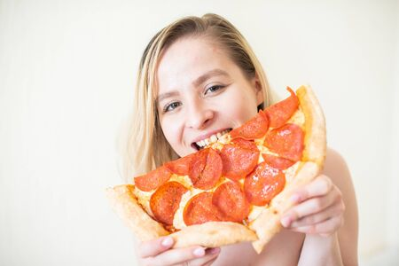 European girl with short hair posing with pieces of delicious pizza.