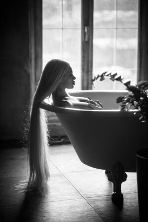 A beautiful woman with gorgeous long blond hair is relaxing in the bath. Silhouette of a woman in profile lying in the bathroom.