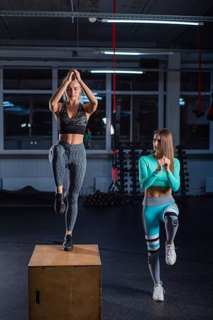 Fit young woman doing box jumping on dark background with copy space. Female trainer conducts a circular training for a young beautiful blonde. High jump on one foot on a box.