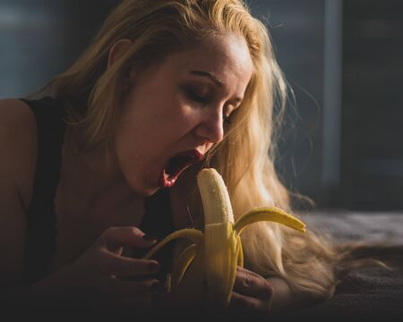 A girl with long blond hair looks at a big banana. Opens her mouth and presents oral