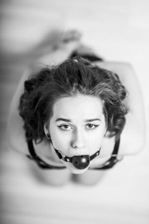 Slavery in society. The girl is on her knees with a gag in her mouth. Sexual bdsm toy. Woman slavery. Slave attire for playing bdsm games. Frightened slave. Black leather bondage with gag. Scared hostage