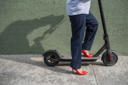 Young woman in formal wear on red hight heels is standing on electrical scooter. Close-up of female legs. A business woman in a trouser suit and red shoes moves around the city on an electric scooter Stock Photo