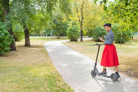 A young woman with purple hair is riding an electric scooter in the park. Stylish girl with a shaven temple in a checkered shirt, a long red skirt and bow-tie writes a message on a smartphone. Hipster
