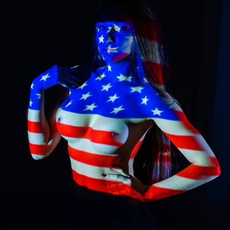 Drawing of the American flag on a naked female body. Body art symbolism of the United States of America.
