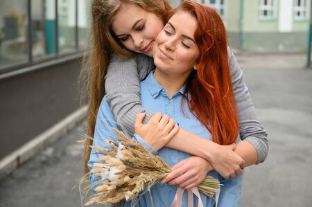 Same-sex relationships. Happy couple with dried flowers. The girl gently hugs the red-haired girlfriend from behind. Close up to a pair of hands. LGBT