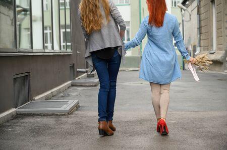 Relaciones del mismo sexo. Feliz pareja caminando por la calle cogidos de la mano. Las espaldas de dos hermosas mujeres en una cita con un ramo de flores secas. LGBT. Foto de archivo