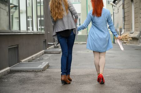 Same-sex relationships. Happy couple walking down the street holding hands. The backs of two beautiful women on a date with a bouquet of dried flowers. LGBT. Stockfoto