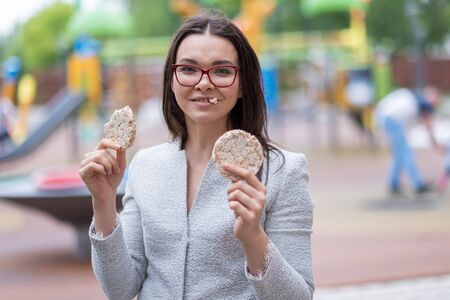 A young girl in glasses, eating round bread on the street.