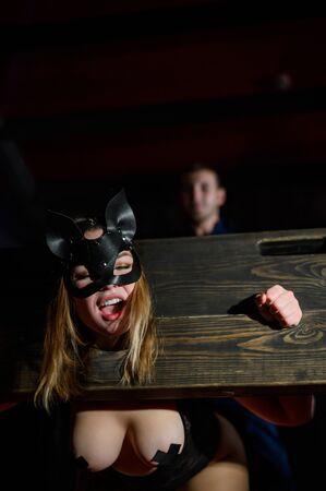 nastri. Una donna è imprigionata in una gogna di legno durante i giochi. BDSM Fantasie erotiche. Subordinazione. Giocattoli per adulti. La maschera del gatto. L'uomo in camicia domina. Archivio Fotografico