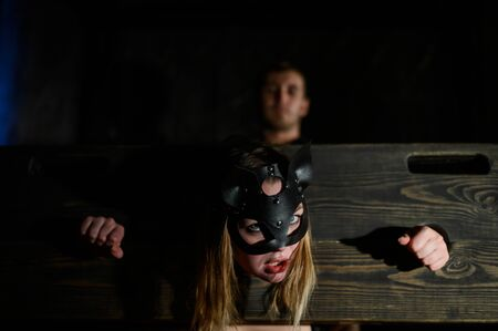 tapes. A woman is imprisoned in a wooden pillory during games. BDSM Erotic fantasies. Subordination. Toys for adults. The mask of the cat. The man in the shirt dominates.
