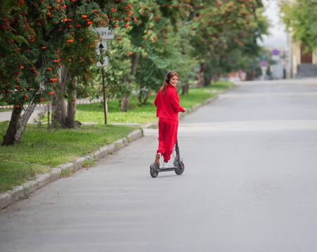 Red-haired girl in a red tracksuit drives an electric scooter. A young woman in oversized clothes rides around the city and listens to music using wireless headphones. View from the back