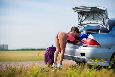 A woman in a seductive bikini is looking for things in the trunk on the side of the road. Elastic buttocks. Fitness bikini. Back view. A girl in the countryside loads suitcases into a car.