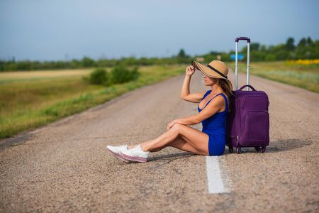 A woman in a hat and with a big bag sits on the pavement. Girl in a blue tight-fitting dress with a purple suitcase on the roadway. A brunette with a sports figure is waiting for a bus 写真素材