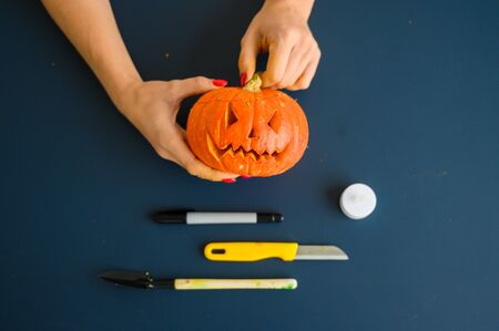 Woman holds a little pumpkin over black background. Halloween concept, flat lay, top view. Candle, pen, knife and pumpkin in hand on a black table.