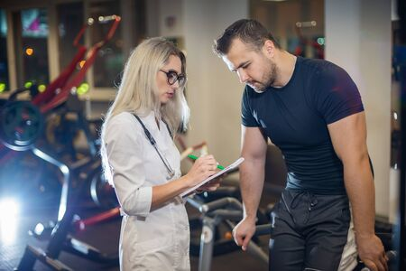 Medical examination. heart rate The doctor measures the pulse during a stress test. A female doctor measures a male athletes heart rate during classes on a treadmill. Standard-Bild