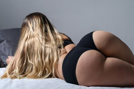A blonde with long hair in black underwear is lying on the bed. Rear view of a girl in thong sleeping on a gray plaid. A figured woman with wide hips, a big booty and a narrow waist. Close-up.