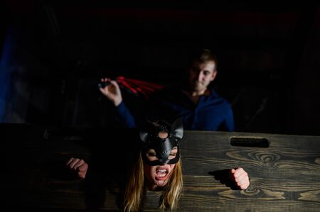 nipple tapes. A woman is imprisoned in a wooden pillory during sexual games. BDSM Erotic fantasies. Subordination. Toys for adults. The mask of the cat. The man in the shirt dominates.