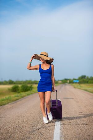 A woman in a hat and with a big bag is walking along the roadway. Girl in a blue tight-fitting dress with a purple suitcase on the track. Brunette with a sports figure on the road.
