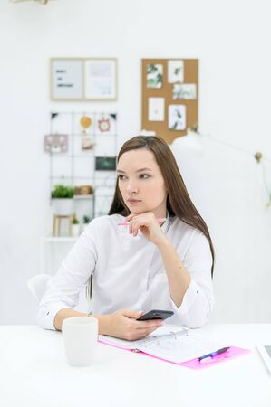 A young woman in a white shirt sits at a desk with a phone in her hands and plans a schedule. Female office worker makes a pen in the organizer. Paper notebook for notes.