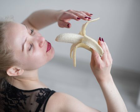 The blonde in black lace underwear erotically eats a banana. Attractive woman with sensual red lips sexually sucks and licks a banana. Oral pleasure.