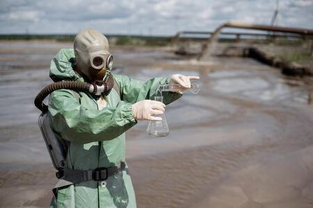 A scientist takes a sample of water from a reservoir after the release of chemical waste. A man in a respirator and a green protective suit from radiation. Water analysis experts. Mask