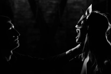 A man in a shirt holds a submissive lover by the neck. A woman in a leather cat mask bites a leather whip. BDSM Games for adults. Sensual lips. Black and white. Stock Photo