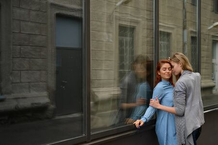 Same-sex relationships. Portrait of two young lesbians passionately hugging and standing against a mirror wall. Loving couple of gay women standing on the street and showing feelings.