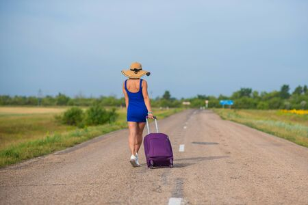 A woman in a hat and with a big bag is walking along the roadway. Girl in a blue tight-fitting dress with a purple suitcase on the track. Brunette with a sports figure on the road