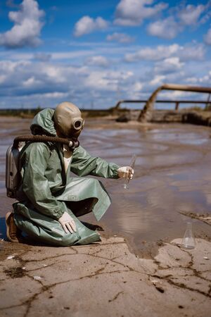 A scientist takes a sample of water after the release of chemical waste. A man in a respirator and a green protective suit from radiation. Water analysis experts. Mask. Ecological catastrophy. Banque d'images
