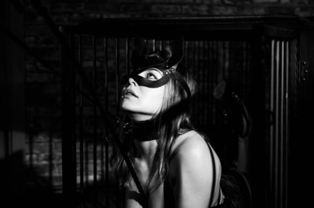 BDSM A woman in a leather cat mask on a leash in an iron cage obeys her lover. Role-playing games for adults. The man dominates and punishes the mistress. Monochrome photo. Stock Photo