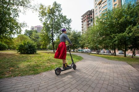 A young woman with purple hair rides an electric scooter in a park. A stylish girl with a shaved temple in a plaid shirt, a long red skirt and a bow tie is riding around the city on a modern device.