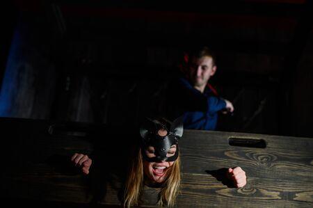 nastri. Una donna è imprigionata in una gogna di legno durante i giochi. BDSM Fantasie erotiche. Subordinazione. Giocattoli per adulti. La maschera del gatto. L'uomo in camicia domina.